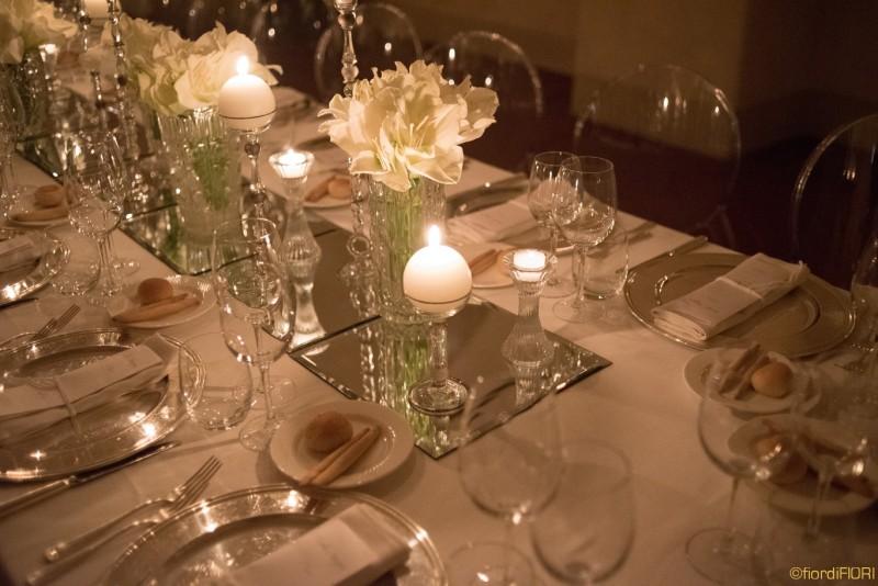 Tavolo imperiale con fiori bianchi e candele di varia forma e altezza
